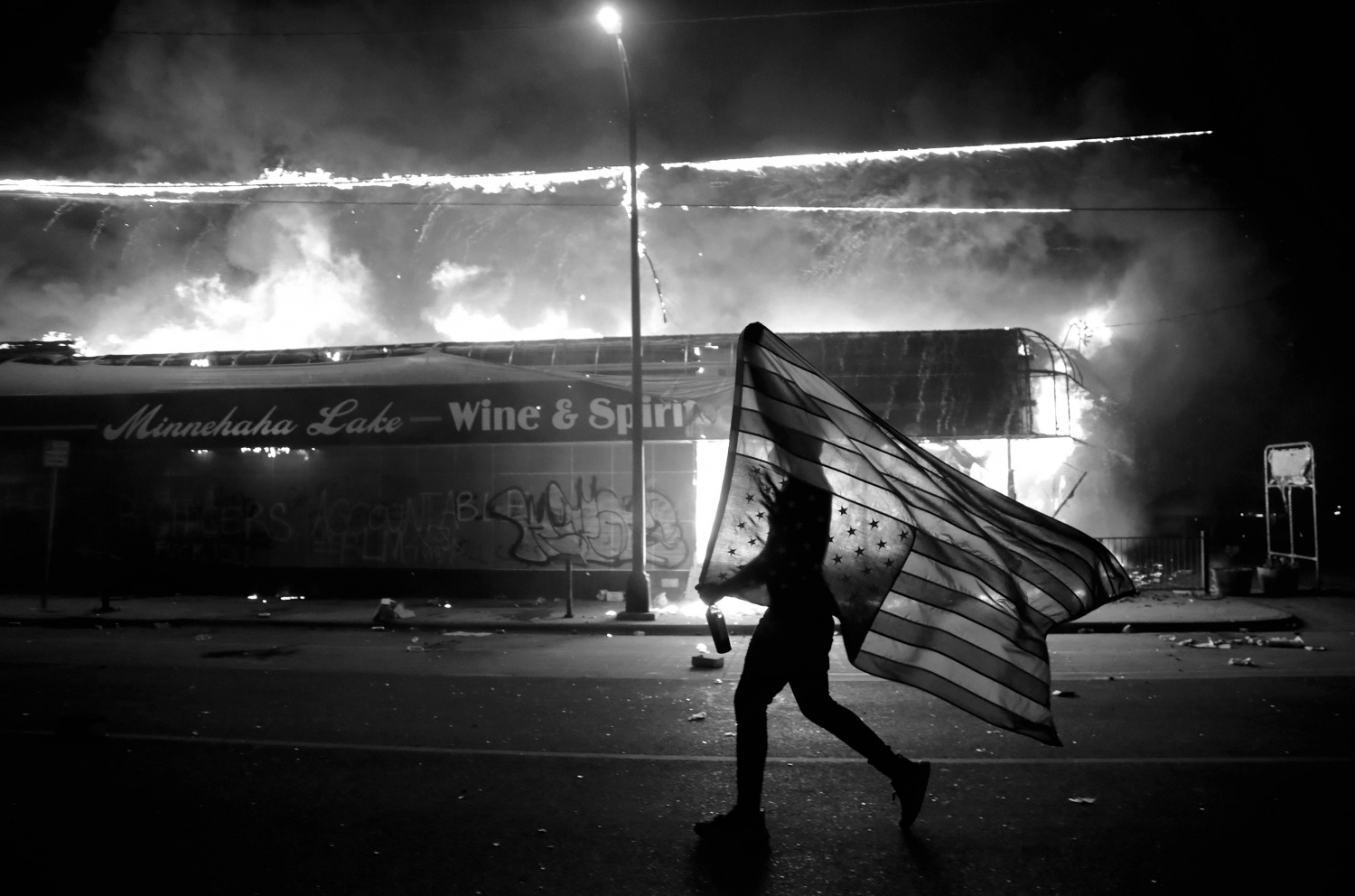 Protester carries the carries a U.S. flag upside, a sign of distress, next to a burning building, in Minneapolis. Protests over the death of George Floyd, a black man who died in police custody Monday, broke out in Minneapolis for a third straight nightPolice Death, Minneapolis, United States - 28 May 2020