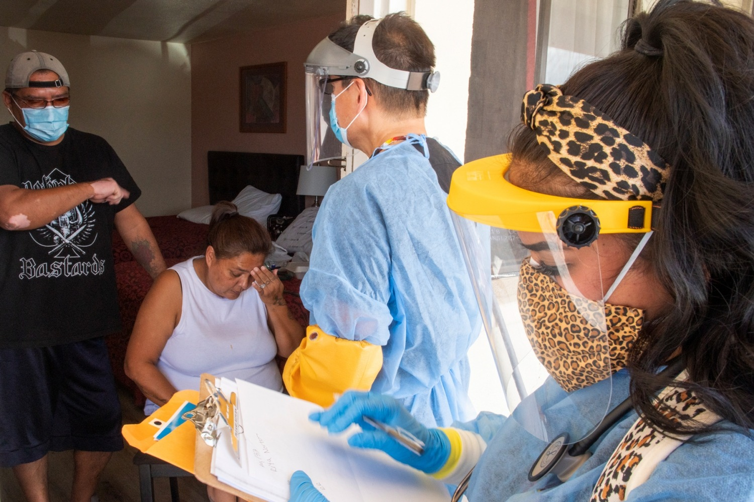 Dr. Caleb Lauber and Medical Assistant Shaniya Wood checking on Roger Bydone and Rita Norton, patients who may be COVID-19 positive, quarantined in a motel in Gallup.