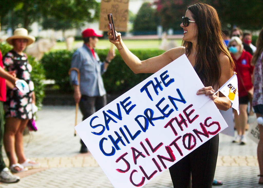 """A protester holds a sign that reads """"Save the children, jail the Clintons,"""" during the Save Our Children Rally in Coolidge Park on Saturday, Aug. 22, 2020, in Chattanooga, Tenn. (Troy Stolt/Chattanooga Times Free Press via AP)"""