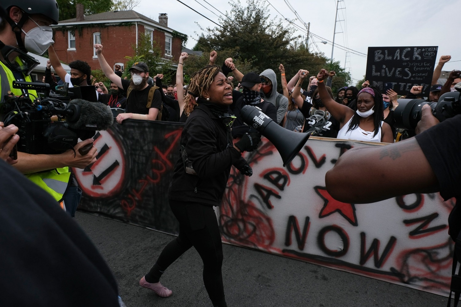 """A protestor calls for the crowd to """"Say Her Name Breonna Taylor"""" while marching in downtown Louisville, Kentucky, on September 23, 2020, after a judge announced the charges brought by a grand jury against Detective Brett Hankison, one of three police officers involved in the fatal shooting of Breonna Taylor in March. - Hankison was charged today, September 23, with three counts of """"wanton endangerment"""" in connection with the shooting of Taylor, a 26-year-old black woman whose name has become a rallying cry for the Black Lives Matter movement. (Photo by Jeff Dean / AFP) (Photo by JEFF DEAN/AFP via Getty Images)"""